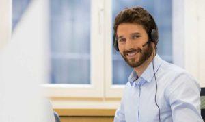 Das Bild zeigt einen freundlichen Mann, der ein Headset auf seinem Kopf trägt. Der Mann ist ein Telefonist. Das Bild ist im Hintergrund von dem Formular, den man ausfüllt, um einen Rückruf zu bekommen.